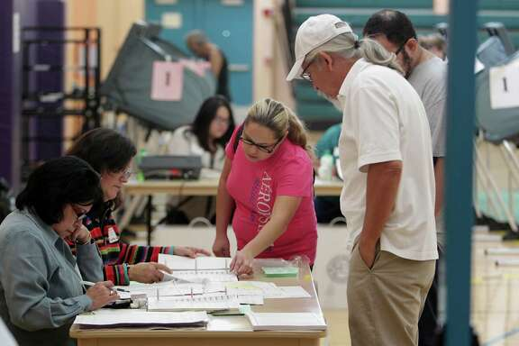 Poll workers sign in voters at the Denver Harbor Park Community Center on Tuesday. A new state law requires residents to produce photo identification before casting their ballots on Election Day.