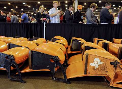 People line up to buy stadium seats at a sale and auction of Houston Astrodome furniture, appliances, Astroturf and staff uniforms on Saturday, Nov. 2, 2013, at the Reliant Center in Houston. The Astrodome was the world's first multipurpose domed stadium and was once home to the Astros and the Oilers. The stadium has been closed to all events since 2009. (AP Photo/Pat Sullivan) Photo: Associated Press / AP