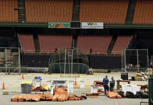 Workmen clean out the Astrodome on Tuesday as voters decided its fate. Thousands of people Saturday bought stadium seats and other items at a sale of Astrodome memorabilia.