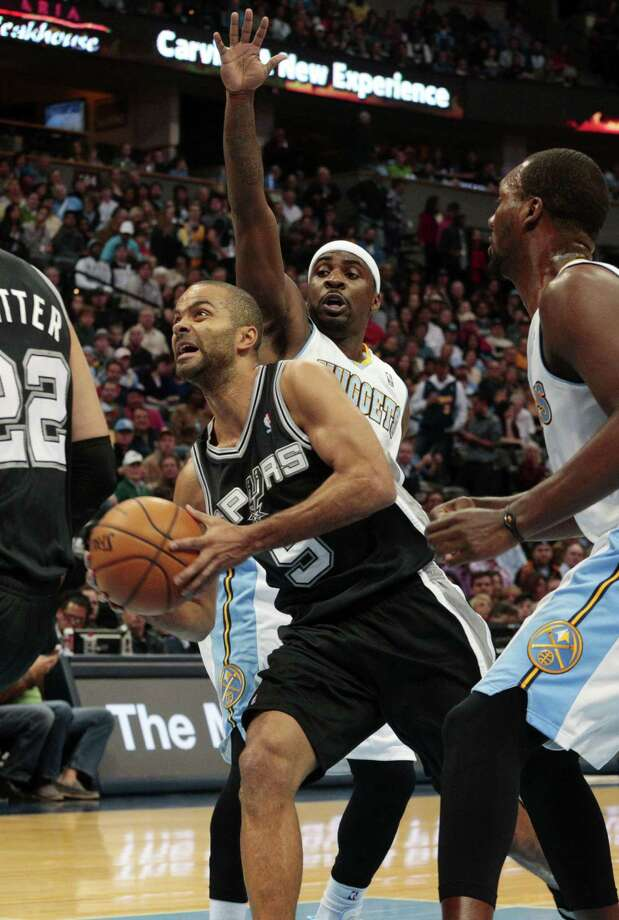 Spurs point guard Tony Parker slices through the lane past the Nuggets' Ty Lawson during the first quarter in Denver. Parker finished with 24 points, six assists and three rebounds. Photo: Joe Mahoney / Associated Press