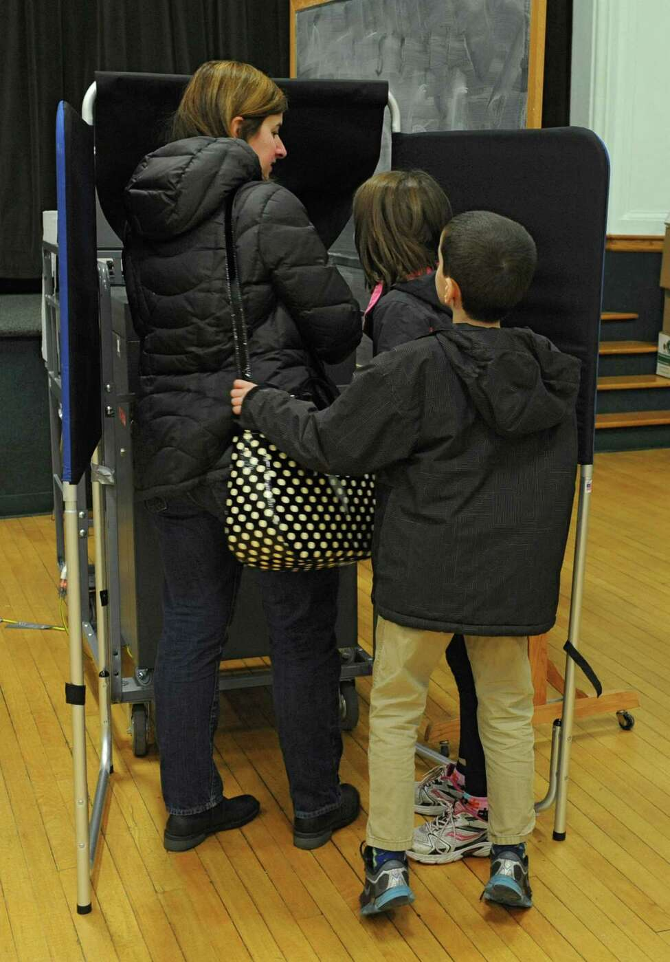 Carol Roeder of Delmar votes while her two children Gillian, 11, center, and Griffin, 9, watch at Bethlehem Town Hall on election day Tuesday, Nov. 5, 2013 in Delmar, N.Y. (Lori Van Buren / Times Union)