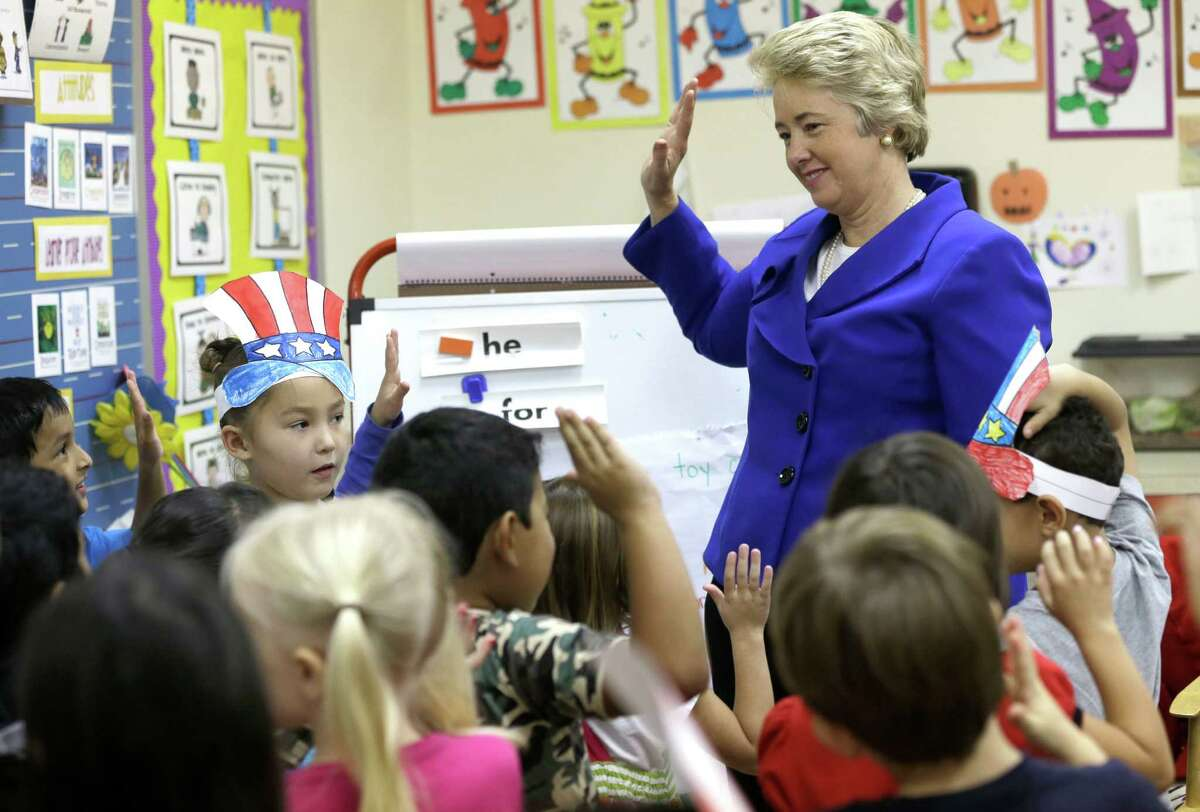 Houston Mayor Annise Parker, right, asks a group of kindergarten students Tuesday, Nov. 5, 2013, in Houston, to promise to vote when they turn 18. Parker was outside talking to voters when a teacher asked her to speak to her class. Parker is running for re-election against Ben Hall. (AP Photo/Pat Sullivan)