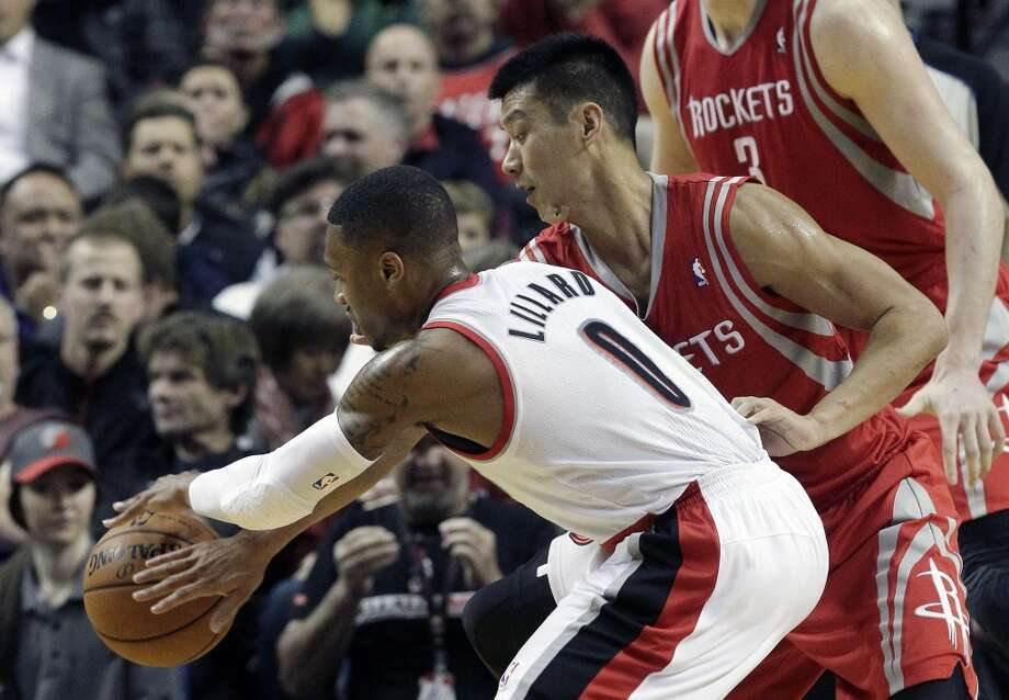 Rockets guard Jeremy Lin, right, reaches in to knock the ball away from Trail Blazers guard Damian Lillard. Photo: Don Ryan, Associated Press