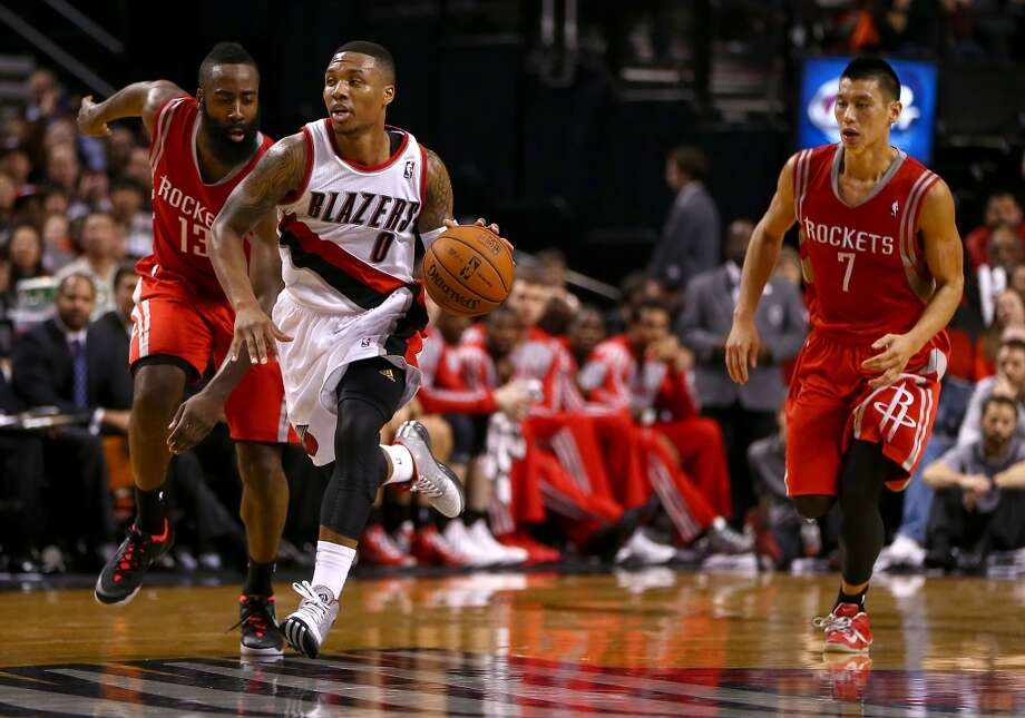 Damian Lilliard #0 of the Trail Blazers dribbles the ball against Jeremy Lin #7 and James Harden #13 of the Rockets. Photo: Jonathan Ferrey, Getty Images