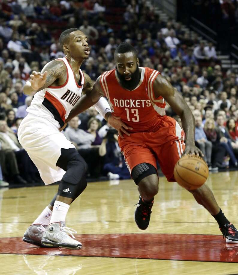 Rockets guard James Harden, right, drives on Trail Blazers guard Damian Lillard. Photo: Don Ryan, Associated Press