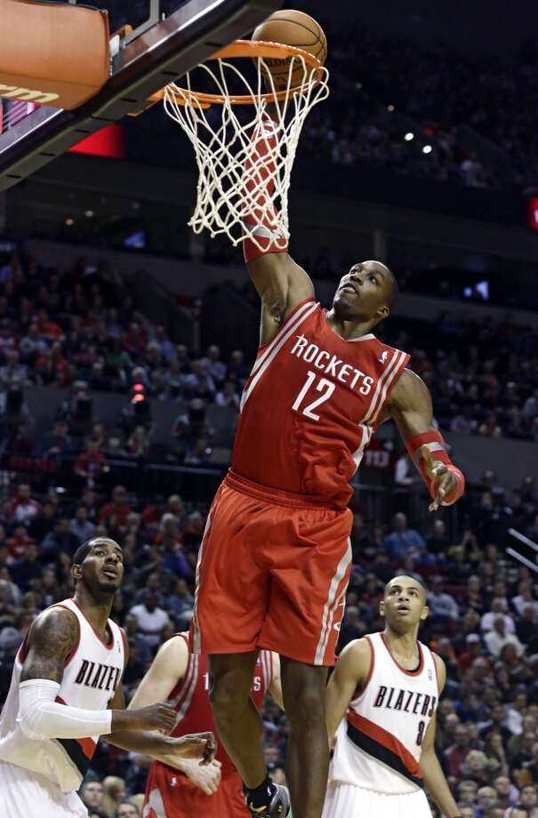 Rockets forward Dwight Howard, center, goes to the basket as LaMarcus Aldridge, left, and Nicolas Batum watch. Photo: Don Ryan, Associated Press