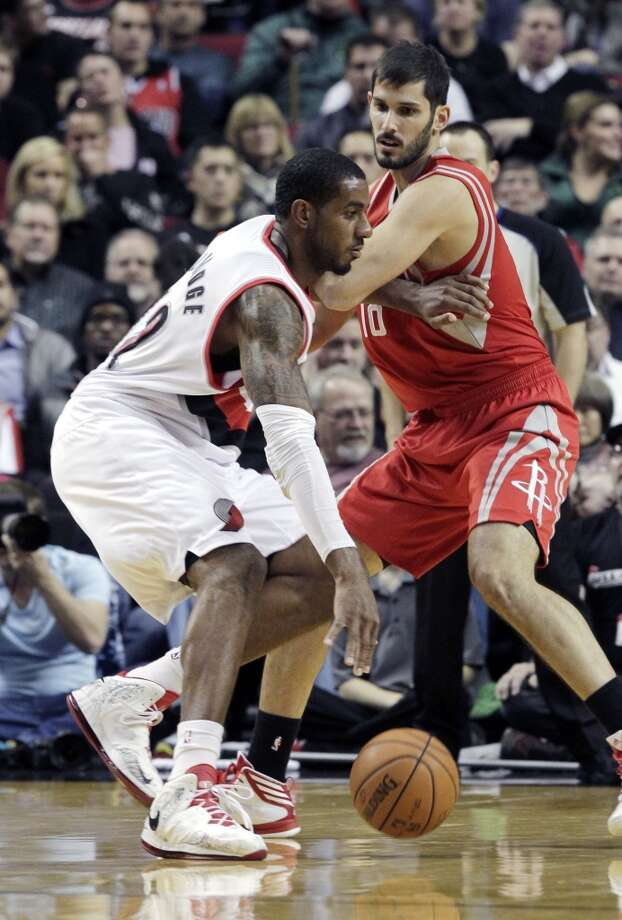 Trail Blazers forward LaMarcus Aldridge, left, drives on rockets forward Omri Casspi. Photo: Don Ryan, Associated Press
