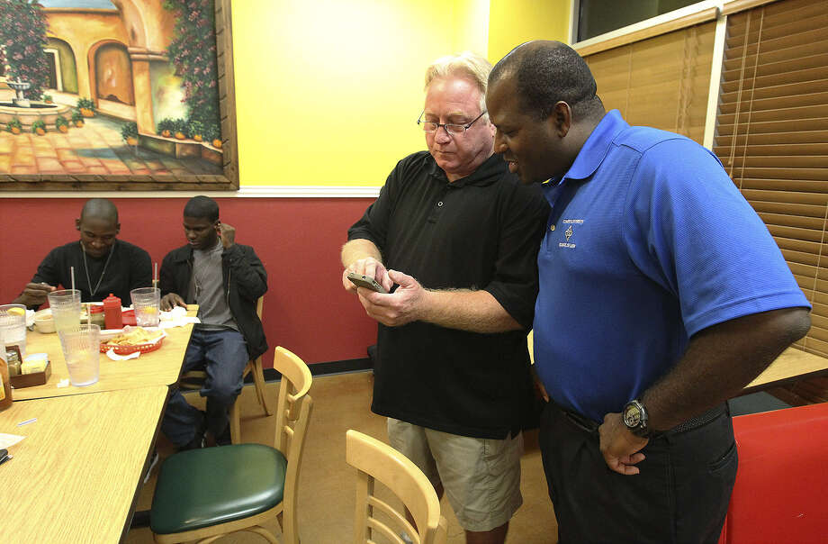 Members of Citizens for Cibolo Andre Larkins (right) and Glen Bonney look at early voting results as the pro-recall group gathers at El Jalisco Mexican Restaurant. Photo: Kin Man Hui / San Antonio Express-News