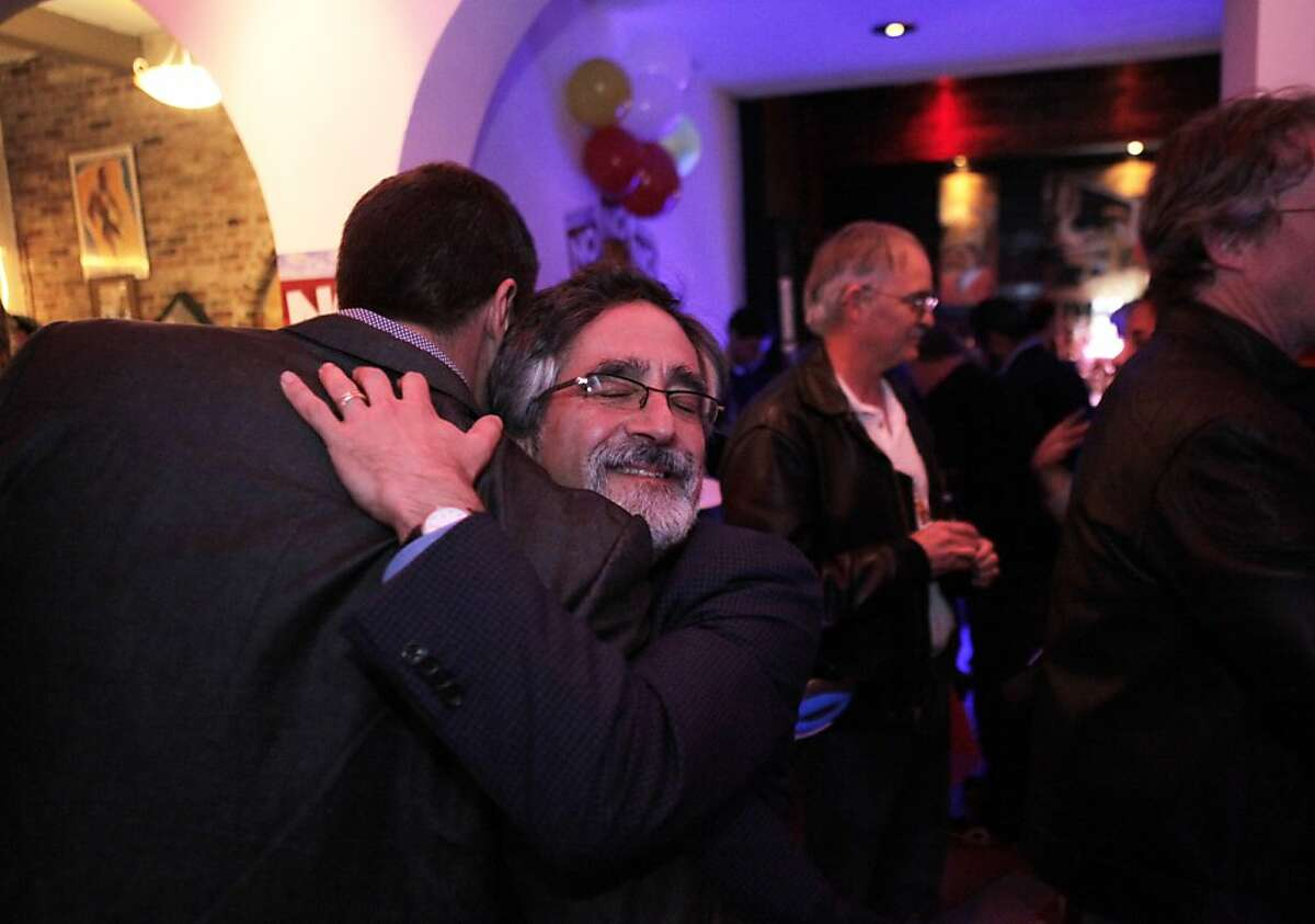 Erich Pearson, left, hugs Aaron Peskin as Peskin arrives at the No on Props B&C victory pary on Tuesday. Opponents of Propositions B & C celebrate after results showed that both measures were defeated on Tuesday, November 5, 2013.