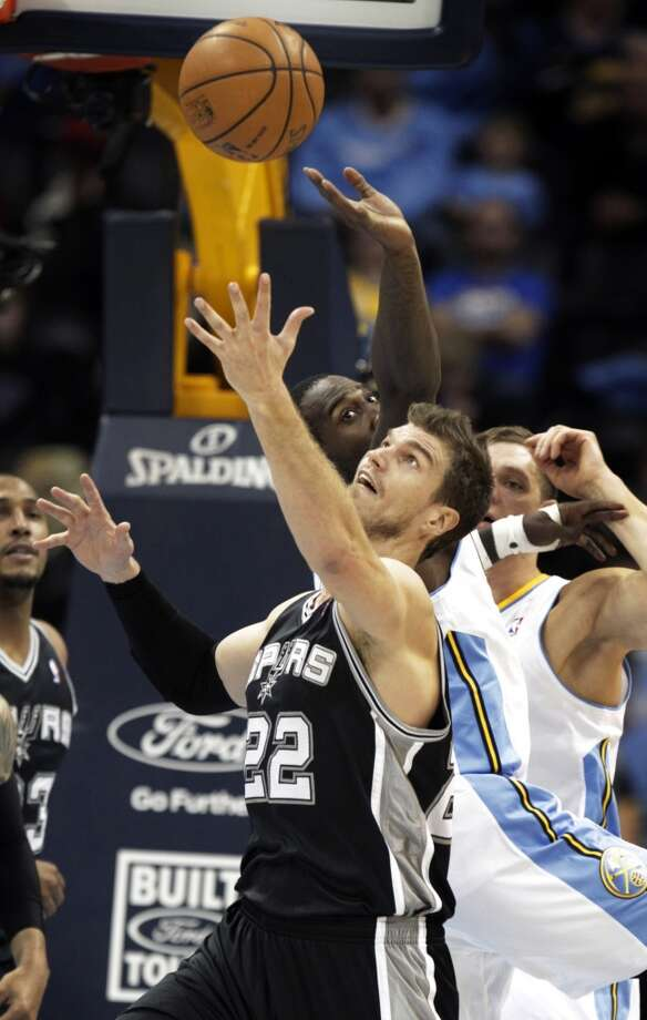 San Antonio Spurs center Tiago Splitter (22) reaches for a loose ball against Denver Nuggets forward J.J. Hickson (7), left, in the second quarter of a basketball game in Denver on Tuesday, Nov. 5, 2013. Photo: Joe Mahoney, Associated Press