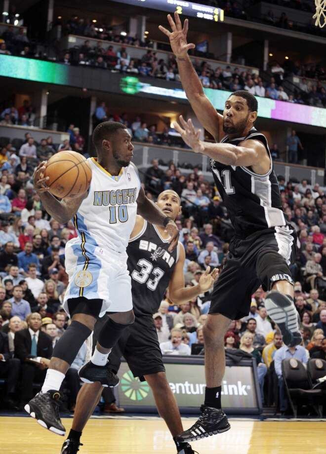 Denver Nuggets guard Nate Robinson (10) passes against San Antonio Spurs forward Tim Duncan (21) and Spurs forward Boris Diaw (33) in the fourth quarter of a basketball game in Denver on Tuesday, Nov. 5, 2013. San Antonio defeated Denver 102-94. Photo: Joe Mahoney, Associated Press