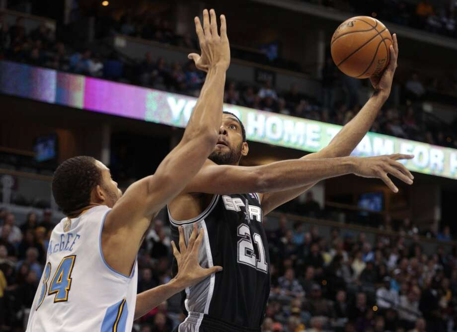San Antonio Spurs forward Tim Duncan (21) shoots against Denver Nuggets center JaVale McGee (34) in the first quarter of a basketball game in Denver on Tuesday, Nov. 5, 2013. Photo: Joe Mahoney, Associated Press