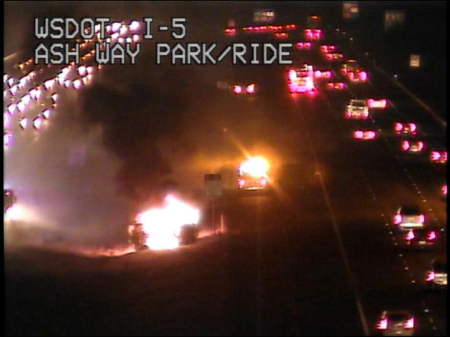 The car is seen burning in the freeway median in this Washington Transportation Department webcam photo.