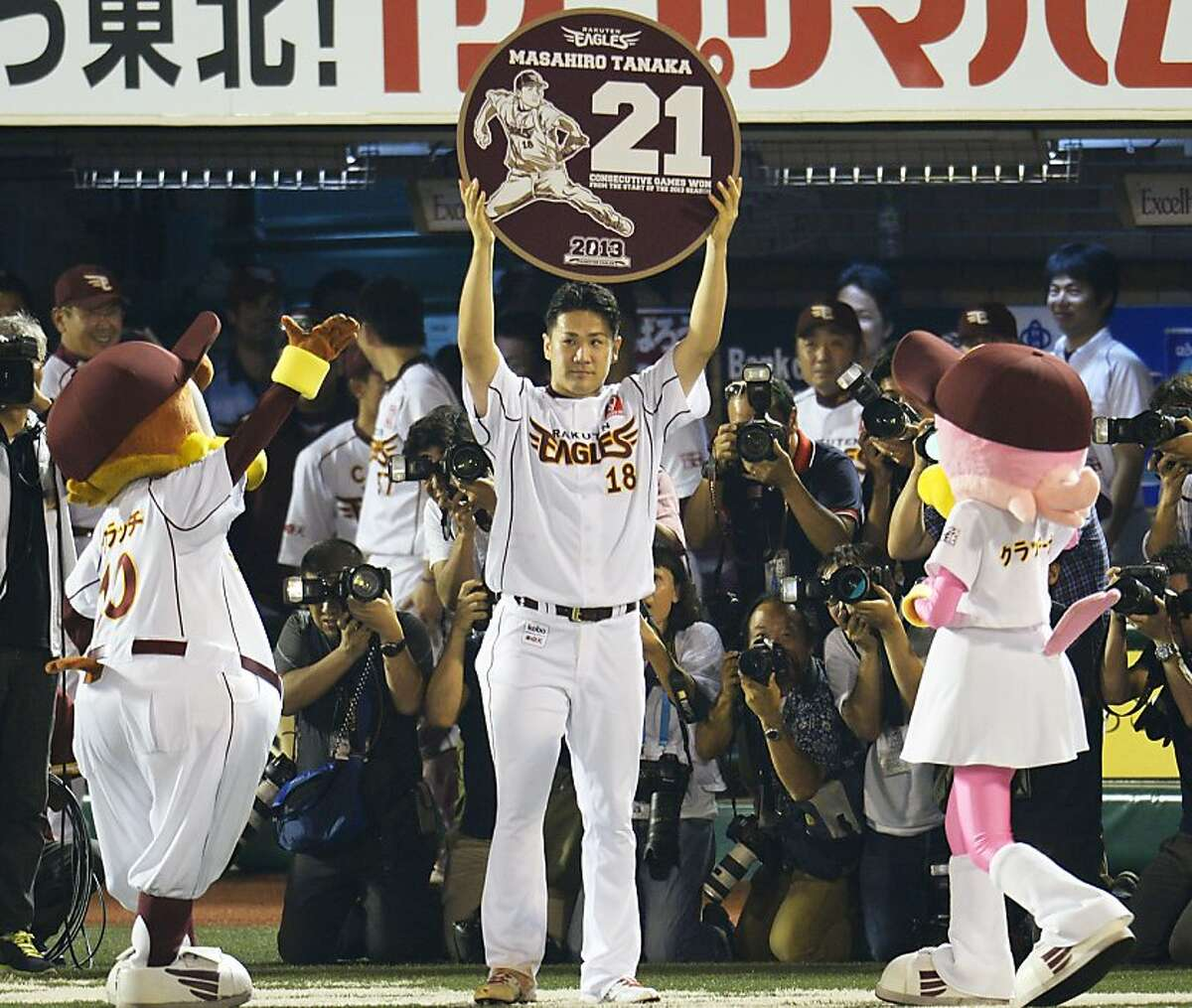 Rakuten Eagles pitcher Masahiro Tanaka raises a special plate written with 21 and his name after pitching against the Orix Buffaloes to win his 21st straight game, setting a new Japanese professional baseball record for consecutive victories in one season, at his team's home stadium in Sendai, northwestern Japan, Friday, Sept. 13, 2013. Tanaka improved to 21-0 on Friday after giving up two runs in a complete game in the Eagles' 6-2 win over the Buffaloes. The previous record of 20 was set in 1957 by Kazuhisa Inao. (AP Photo/Kyodo News) JAPAN OUT, MANDATORY CREDIT
