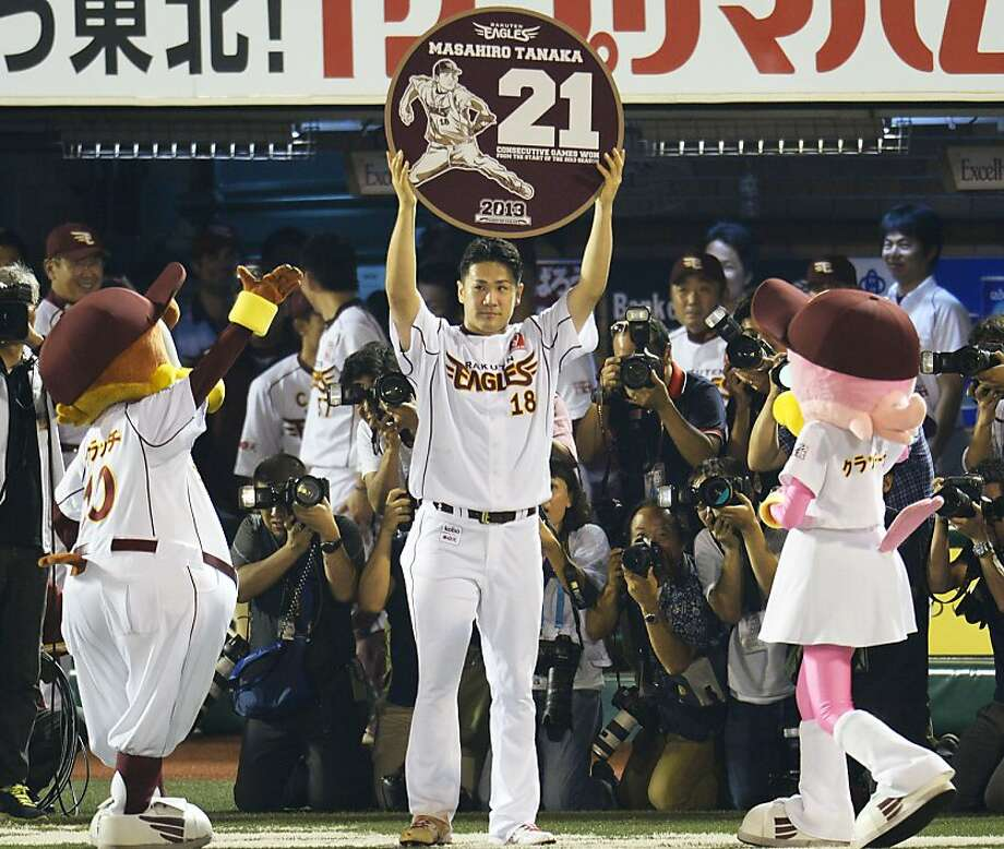 Rakuten Eagles pitcher Masahiro Tanaka raises a special plate written with 21 and his name after pitching against the Orix Buffaloes to win his 21st straight game, setting a new Japanese professional baseball record for consecutive victories in one season, at his team's home stadium in Sendai, northwestern Japan, Friday, Sept. 13, 2013. Tanaka improved to 21-0 on Friday after giving up two runs in a complete game in the Eagles' 6-2 win over the Buffaloes. The previous record of 20 was set in 1957 by Kazuhisa Inao. Photo: Associated Press