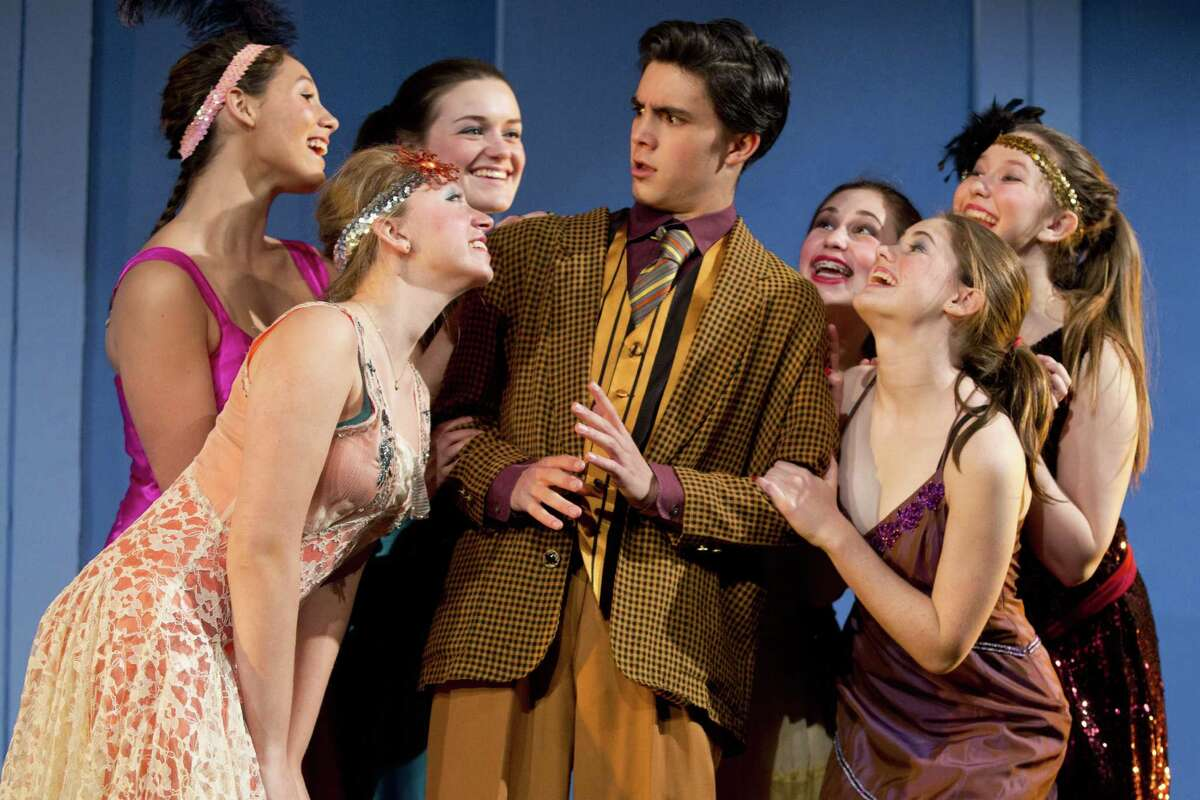 """Nick Ribolla, in his role as Jimmy, is taken back by some of the female attantion lavished on hms in a scene from Staples High School's production of """"Thoroughly Modern Millie."""" Surrounding Ribolla are, from left, Emma Ruchefsky, Sophie DeBruijn, Sarah Quagliarello, Zoe Mezoff, Zoe Fox and Rachel Corbally."""