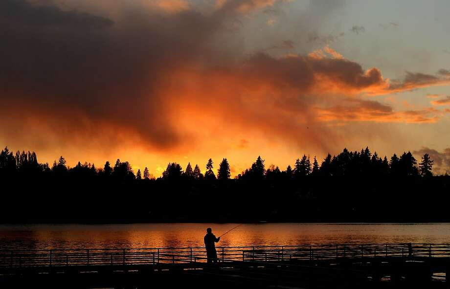 Pier fisherman: Anthony Gastelum fishes the Lions Park Pier at day's end in Bremerton, Wash. Photo: Larry Steagall, Associated Press