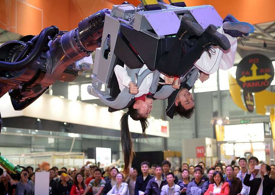 That was fun! You can let us down now, ROBOcoaster ... ROBOcoaster? Hello? Visitors ride in the arm of the ROBOcoaster at the China 