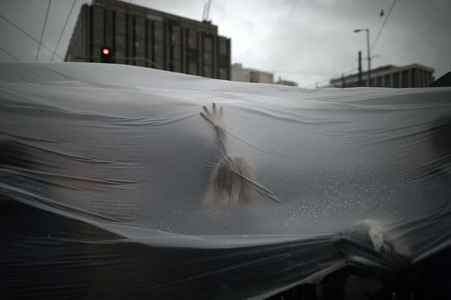 Protesters demonstrateunder a plastic tarp during a rainy 24-hour general strike in Athens. City transit 