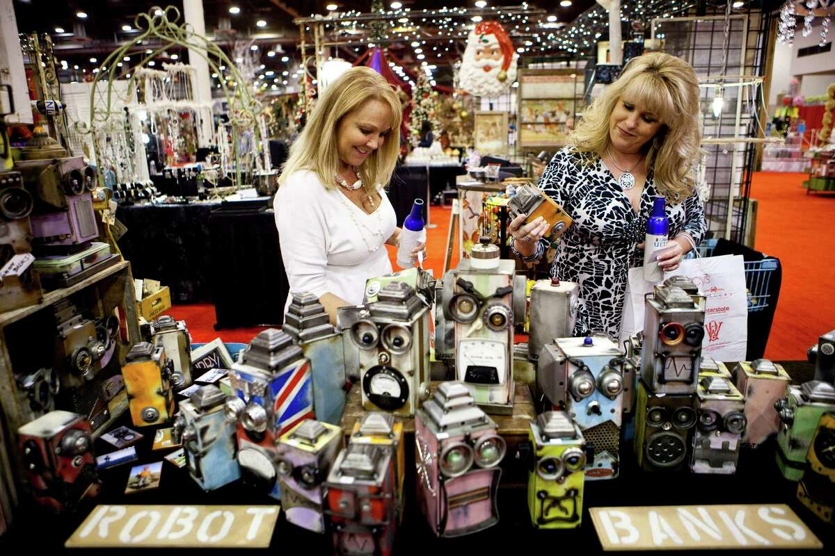 Sharn Edwards, left, and Kim Malone, look at Robot Banks made by Aaron Voight, as they visit the Shabby Chic booth during the 2012 Nutcracker Market's preview night, Wednesday, Nov. 7, 2012, in Houston. The Market will continue until Sunday the 11th.( Nick de la Torre / Houston Chronicle )
