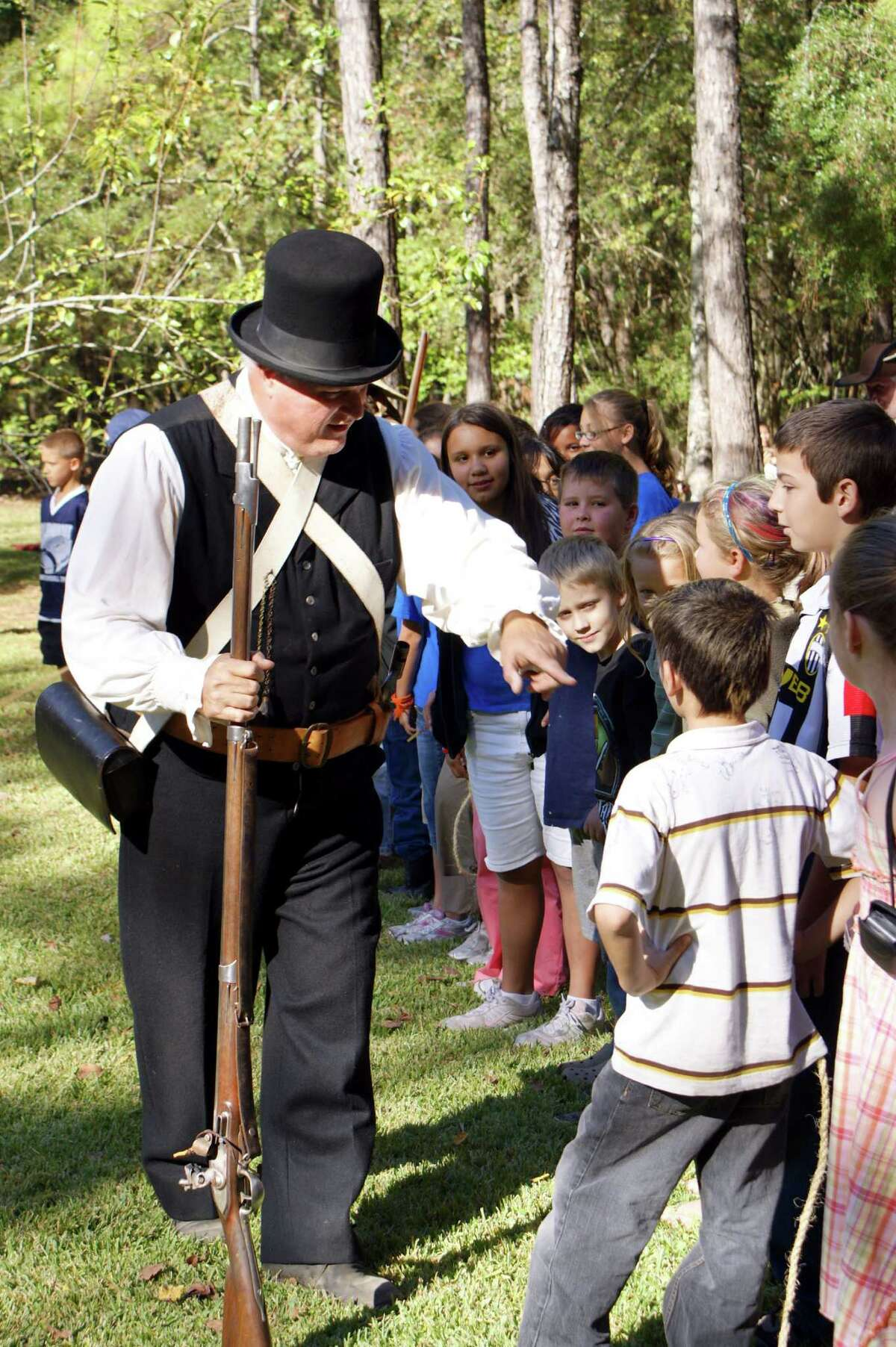 Jesse Jones Park Volunteers President Tom Whitesides dressed as an 1830s Texian musters young recruits for protecting the homestead, a scene set for Pioneer Day to be held Saturday, November 9 from 10 a.m. to 4 p.m.