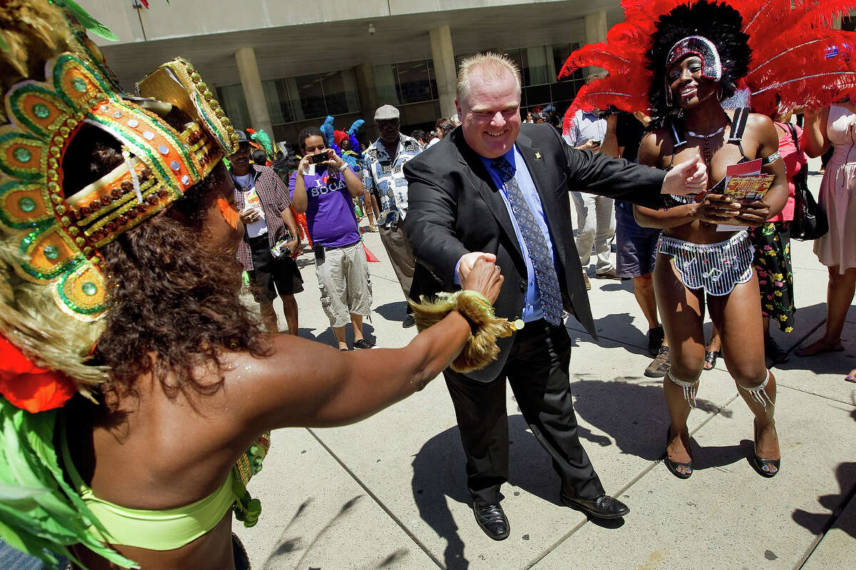 Mikala Moss, of the Bahamas, coaxes Mayor Rob Ford to dance at the Caribbean Carnival launch at Nathan Philips Square. No name of lady on right. July 12, 2011. BERNARD WEIL/TORONTO STAR