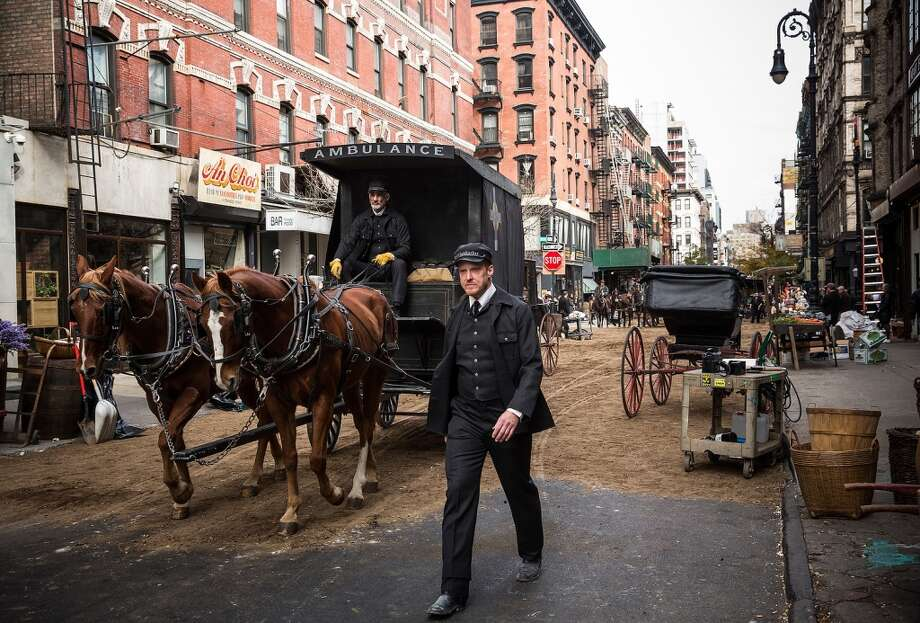 """An actor stands on the set of a television show currently being filmed on November 6, 2013 in the Lower East Side neighborhood of the Manhattan borough of New York City. According to a worker on set, the show is a TV mini-series currently titled """"The Knick,"""" is directed by Steven Sodenburgh and stars Clive Owen. Photo: Andrew Burton, Getty Images"""
