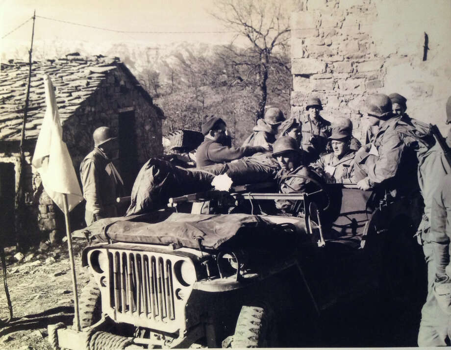 Medics of the 10th Mountain Division load wounded infantry man on a jeep for evacuation. Mt. Belvedere, Italy. Feb. 10, 1945. Photo: Pamela Purdy, Contributed / New Canaan News Contributed
