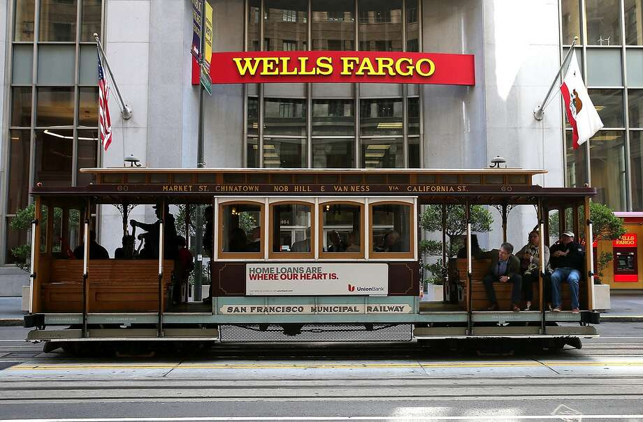 SAN FRANCISCO, CA - OCTOBER 11:  A cable car passes by a Wells Fargo bank on October 11, 2013 in San Francisco, California. Wells Fargo reported a 13 percent increase in third-quarter profits with a net income of $5.6 billion, or 99 cents a share compared to $4.9 billion, or 88 cents a share one year ago.  (Photo by Justin Sullivan/Getty Images) Photo: Justin Sullivan, Getty Images