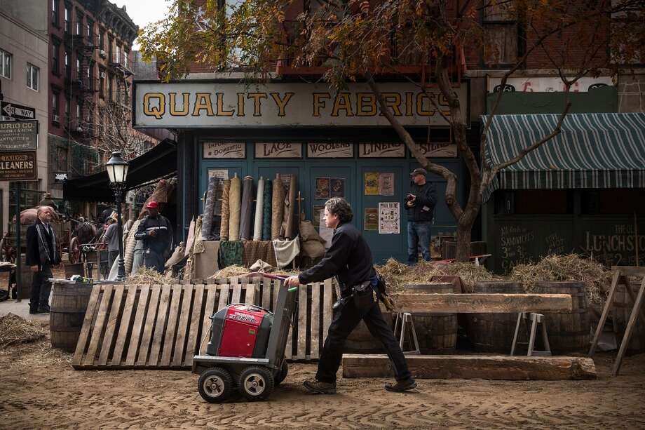 "An worker pushes equipment through a set for a television show currently being filmed on November 6, 2013 in the Lower East Side neighborhood of the Manhattan borough of New York City. According to a worker on set, the show is a TV mini-series currently titled ""The Knick,"" is directed by Steven Sodenburgh and stars Clive Owen. Photo: Andrew Burton, Getty Images"