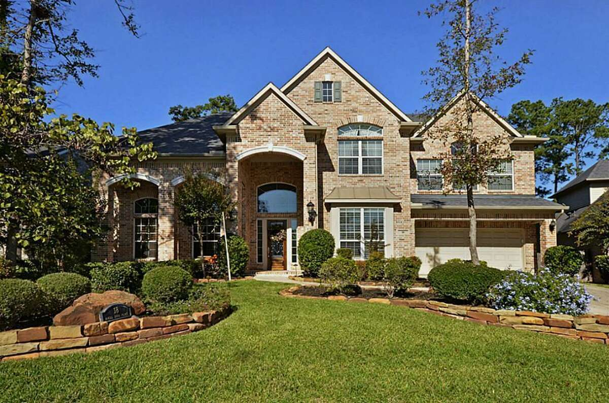 The traditional home features beautiful landscaping.