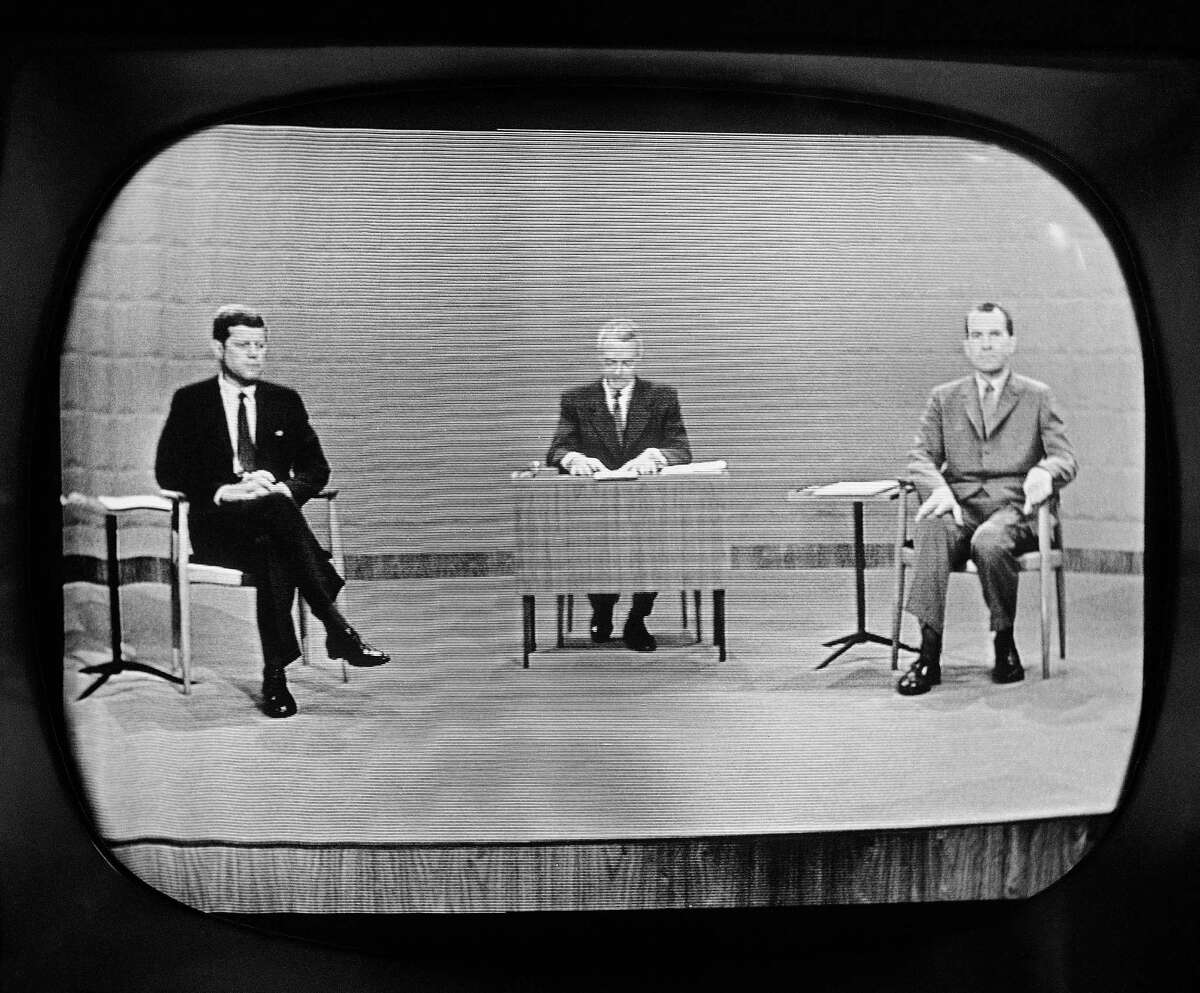 """FILE - In this Sept. 26, 1960 file photo, moderator Howard K. Smith sits between, Sen. John Kennedy, left, and Vice President Richard Nixon as they appear on television studio monitor set during their debate in Chicago. The Kennedy image, the """"mystique"""" that attracts tourists and historians alike, did not begin with his presidency and is in no danger of ending 50 years after his death. The multimedia story began in childhood with newsreels and newspaper coverage of the smiling Kennedy brood, and it continued with books, photographs, movies and finally television, notably the telegenic JFK?s presidential debates with Nixon. (AP Photo)"""