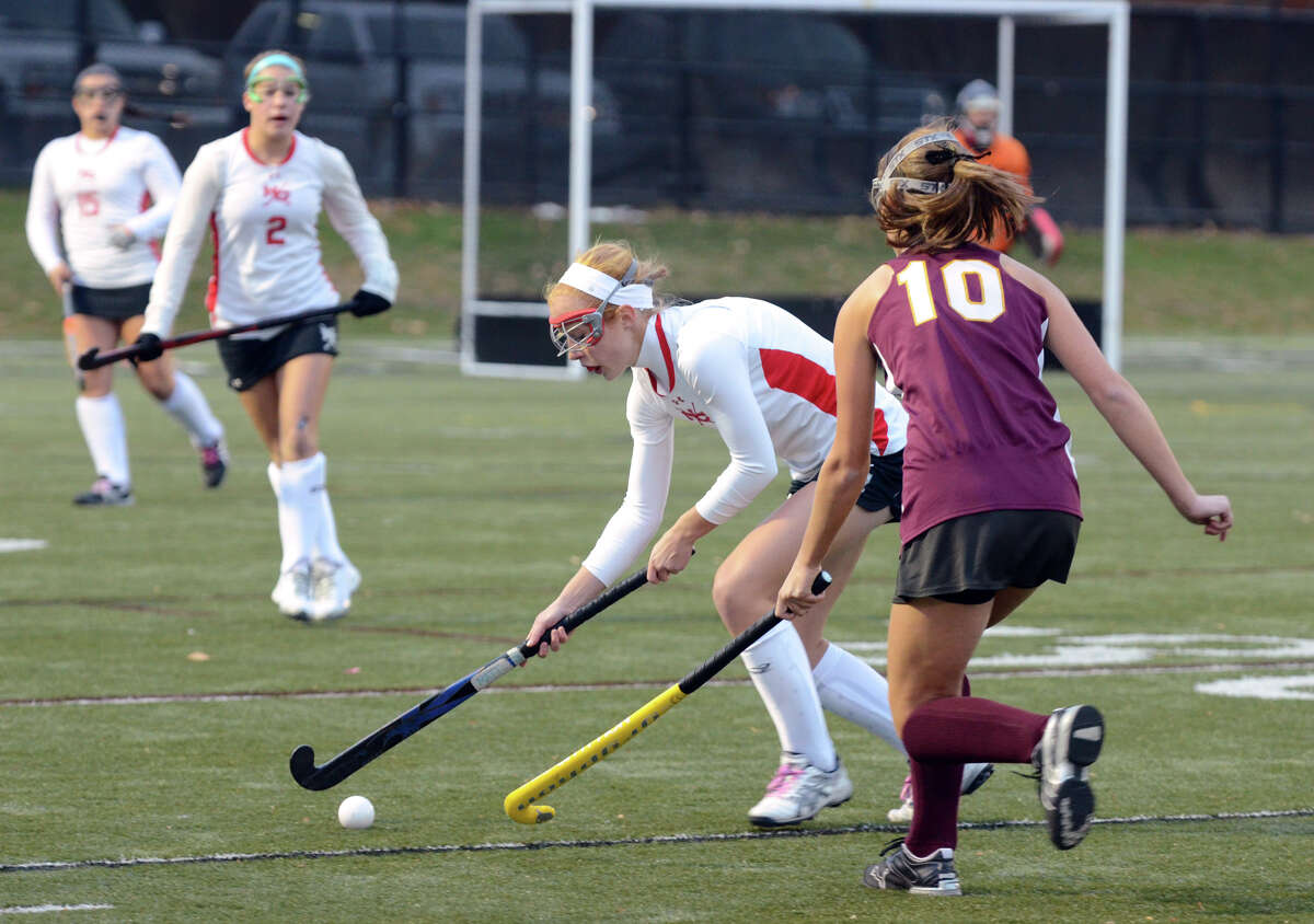 New Canaan's Abbie Jameson (4) controls the ball as South Windsor's Kristen Wnuck (10) defends during the field hockey Class L first round game at Dunning Stadium at New Canaan High School on Wednesday, Nov. 6, 2013.