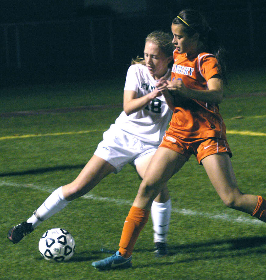Helen Bayers of the Green Wave battles a Danbury player for possession deep in New Milford territory during Wednesday's state tournament match at NMHS. Nov. 6, 2013 Photo: Norm Cummings / The News-Times