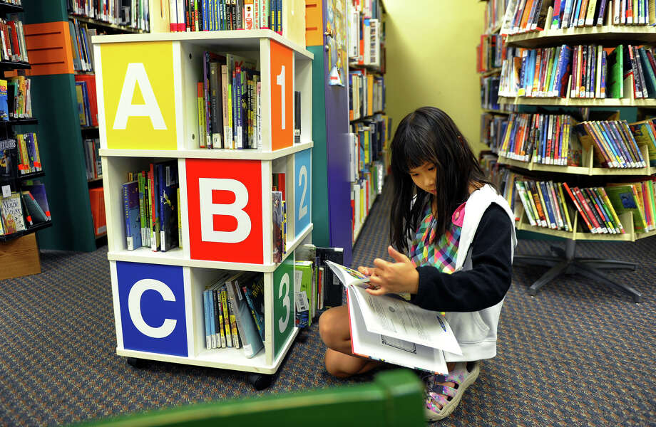 Phuong Tran, 8, of Bridgeport, paruses books in the children's section at Bridgeport City Library's Old Mill Green branch on East Main Street in Bridgeport, Conn. on Wednesday November 6, 2013. Photo: Christian Abraham / Connecticut Post