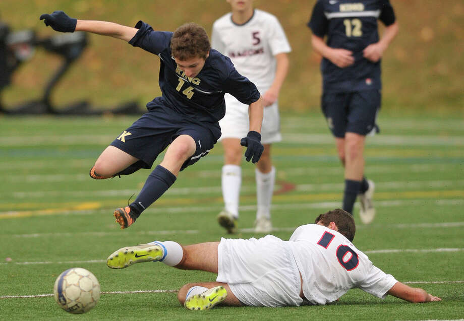 King's Jack Lineberry jumps over the sliding Brendan Bieder, of Greens Farms Academy, during their FAA semifinal game at King school in Stamford, Conn., on Wednesday, Nov. 6, 2013. Greens Farms Academy won, 1-0. Photo: Jason Rearick / Stamford Advocate