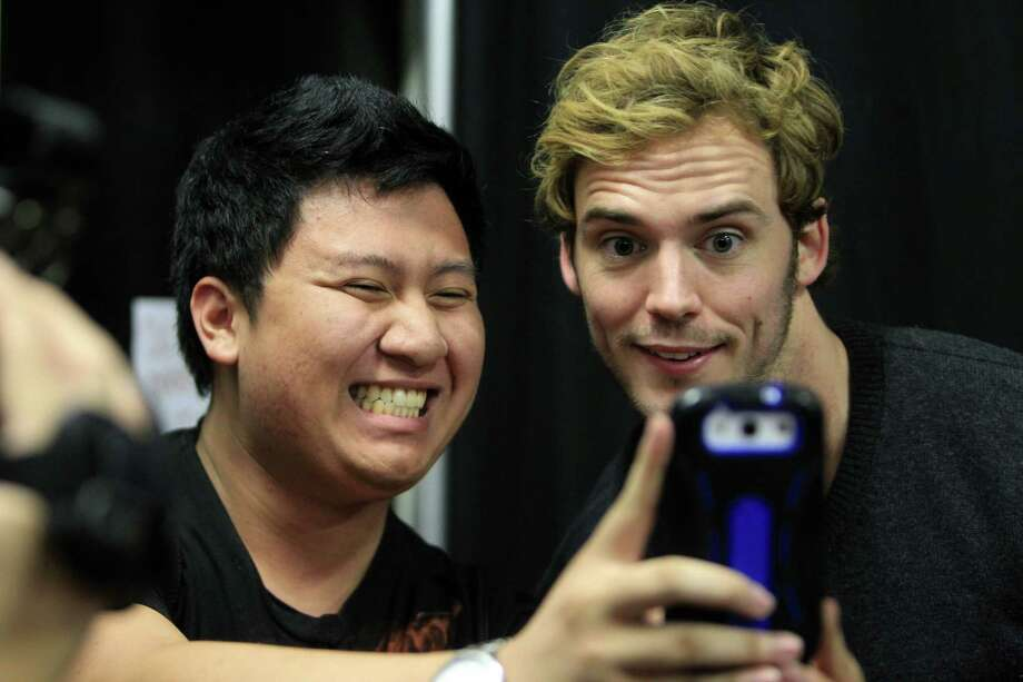 "Sam Claflin, ""Finnick"", greets a fan Eric Pham in the autograph session during The Hunger Games: Catching Fire Victory Tour at the Bayou Music Center on Wednesday, Nov. 6, 2013, in Houston.  The movie will be released worldwide on Nov. 22. Photo: Mayra Beltran, Houston Chronicle / © 2013 Houston Chronicle"