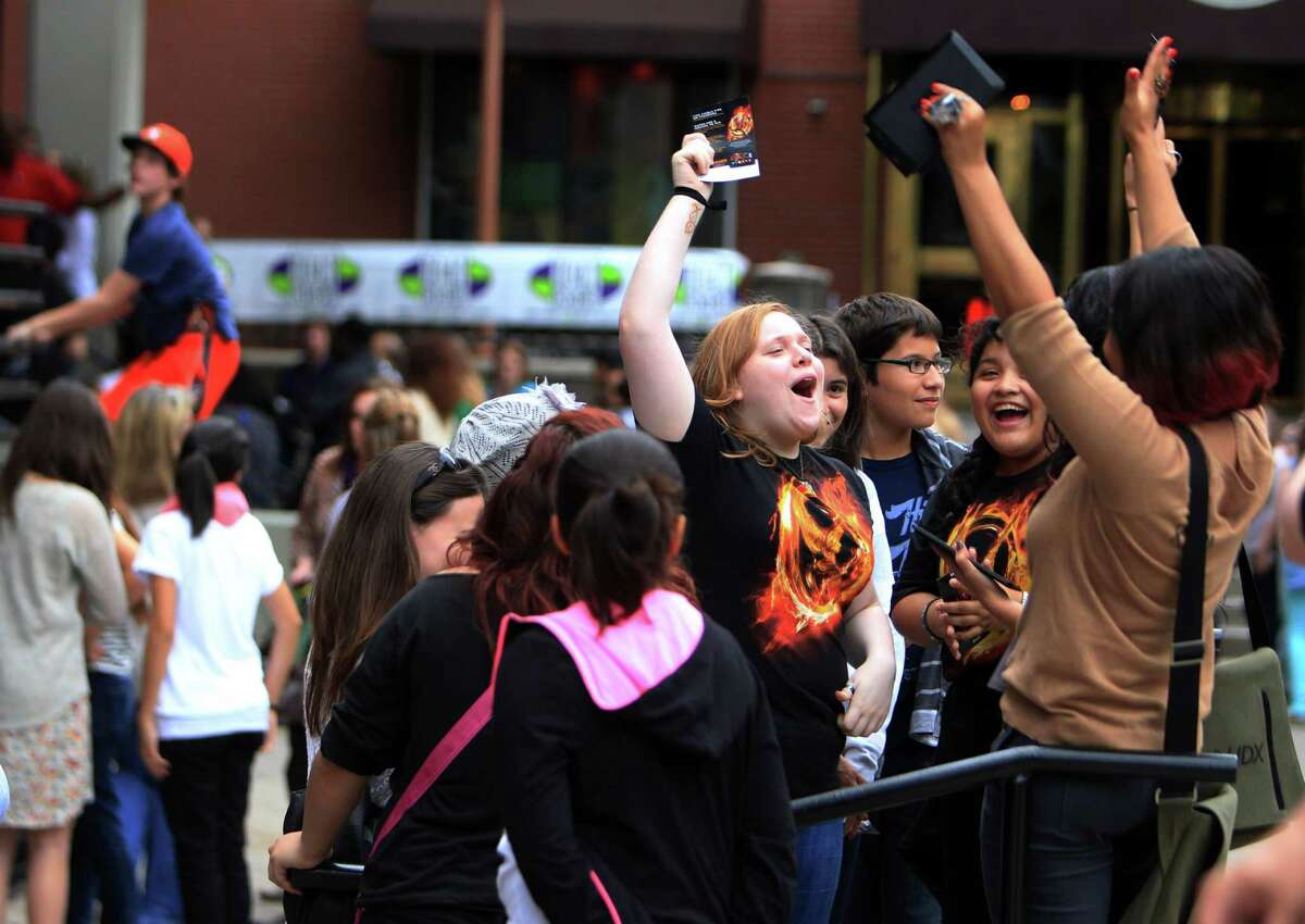 Carly Merritt joins cheering fans who stand in line waiting for the doors to open at the Bayou Music Center for The Hunger Games: Catching Fire Victory Tour.