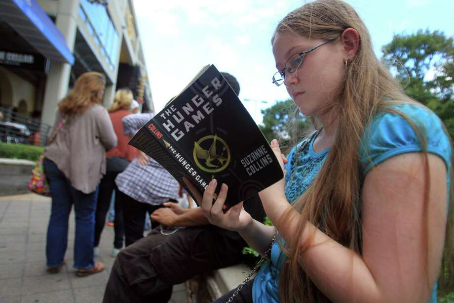 Kaitlyn Mullins, 12, reads her book while waiting for doors to open at the Bayou Music Center for The Hunger Games: Catching Fire Victory Tour. Photo: Mayra Beltran, Houston Chronicle / © 2013 Houston Chronicle