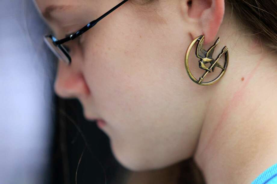 Kaitlyn Mullins, 12, wears the Hunger Games emblem to  The Hunger Games: Catching Fire Victory Tour. Photo: Mayra Beltran, Houston Chronicle / © 2013 Houston Chronicle