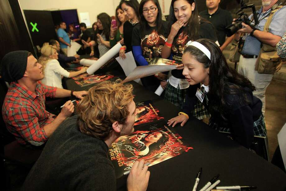 "Sam Claflin, ""Finnick"", signs an autograph for fan Julia Villasenor during The Hunger Games: Catching Fire Victory Tour. Photo: Mayra Beltran, Houston Chronicle / © 2013 Houston Chronicle"