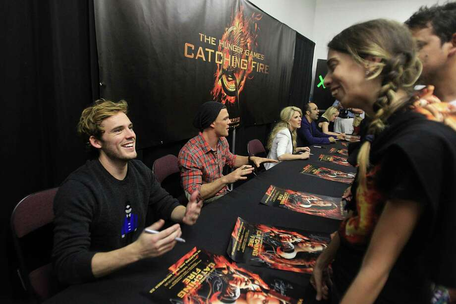 "Sam Claflin, ""Finnick"", greets a fan in the autograph session during The Hunger Games: Catching Fire Victory Tour. Photo: Mayra Beltran, Houston Chronicle / © 2013 Houston Chronicle"