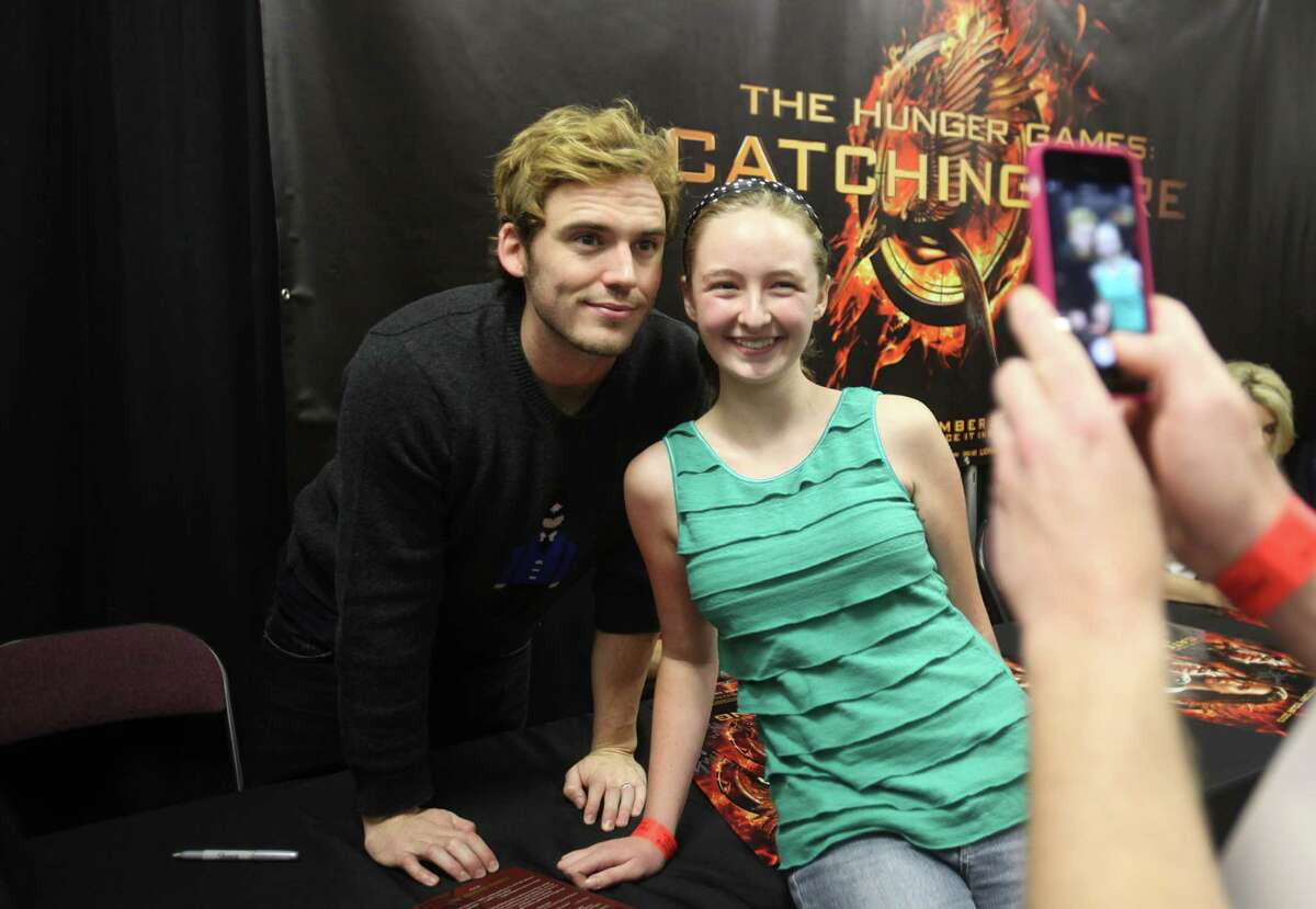 """Sam Claflin, """"Finnick"""", poses with fan Faith Berrigan, 14, during a VIP autograph signing session at The Hunger Games: Catching Fire Victory Tour at the Bayou Music Center."""