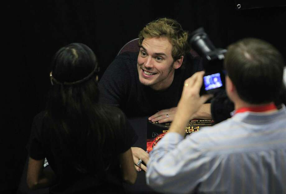 "Sam Claflin, ""Finnick"", greets a fan during The Hunger Games: Catching Fire Victory Tour autograph session. Photo: Mayra Beltran, Houston Chronicle / © 2013 Houston Chronicle"