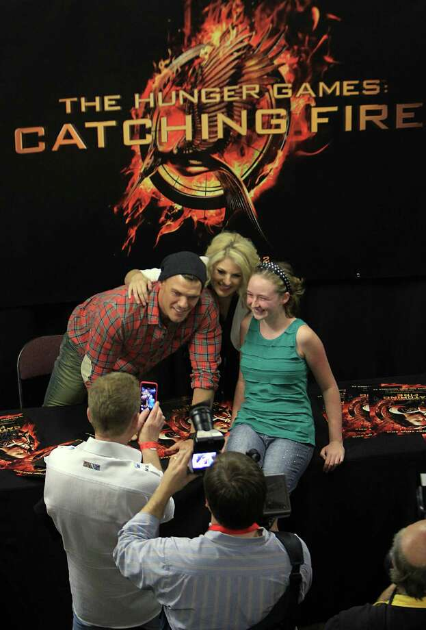 "Alan Ritchson, ""Gloss"", and Stephanie Leigh Schlund, ""Cashmere"", pose with fan Faith Berrigan during The Hunger Games: Catching Fire Victory Tour autograph session at the Bayou Music Center. Photo: Mayra Beltran, Houston Chronicle / © 2013 Houston Chronicle"