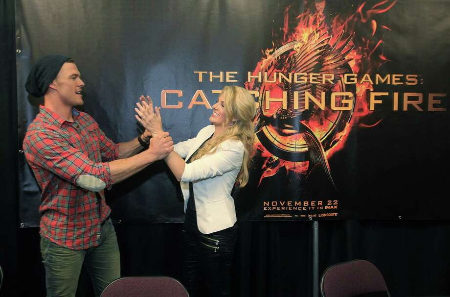 "Alan Ritchson, ""Gloss"", and Stephanie Leigh Schlund,, ""Cashmere"" horseplay upon the conclusion of The Hunger Games: Catching Fire Victory Tour autograph session. Photo: Mayra Beltran, Houston Chronicle / © 2013 Houston Chronicle"