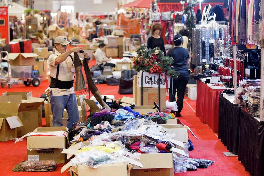 Holding a scarf, Hector Munoz helps stock the Palacio de Plata booth before the 33rd annual Nutcracker Market at Reliant Center Wednesday, Nov. 6, 2013, in Houston. Photo: Johnny Hanson, Houston Chronicle / Houston Chronicle