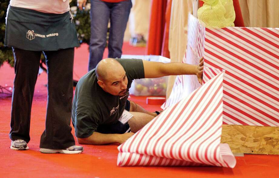 Kris Rodriguez helps decorate the Under Wraps booth in wrapping paper at the 33rd annual Nutcracker Market at Reliant Center Wednesday, Nov. 6, 2013, in Houston. Photo: Johnny Hanson, Houston Chronicle / Houston Chronicle