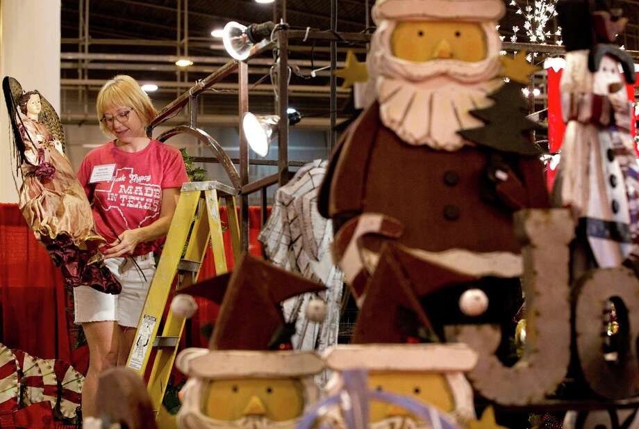 Donna Johnson hangs up a decorative angel in the Market Square Accents and Interiors booth at the 33rd annual Nutcracker Market at Reliant Center Wednesday, Nov. 6, 2013, in Houston. Photo: Johnny Hanson, Houston Chronicle / Houston Chronicle