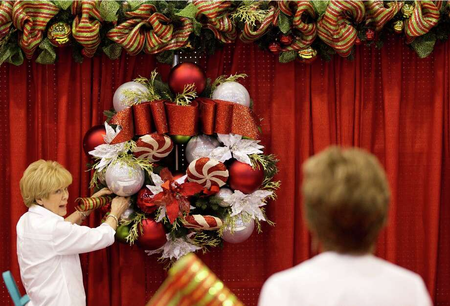Sue Giammalva, left, and Diana Porcarello, adjust a wreath in the Donne di Domani  booth where they sell marinara sauce for charity during the 33rd annual Nutcracker Market at Reliant Center Wednesday, Nov. 6, 2013, in Houston. Photo: Johnny Hanson, Houston Chronicle / Houston Chronicle